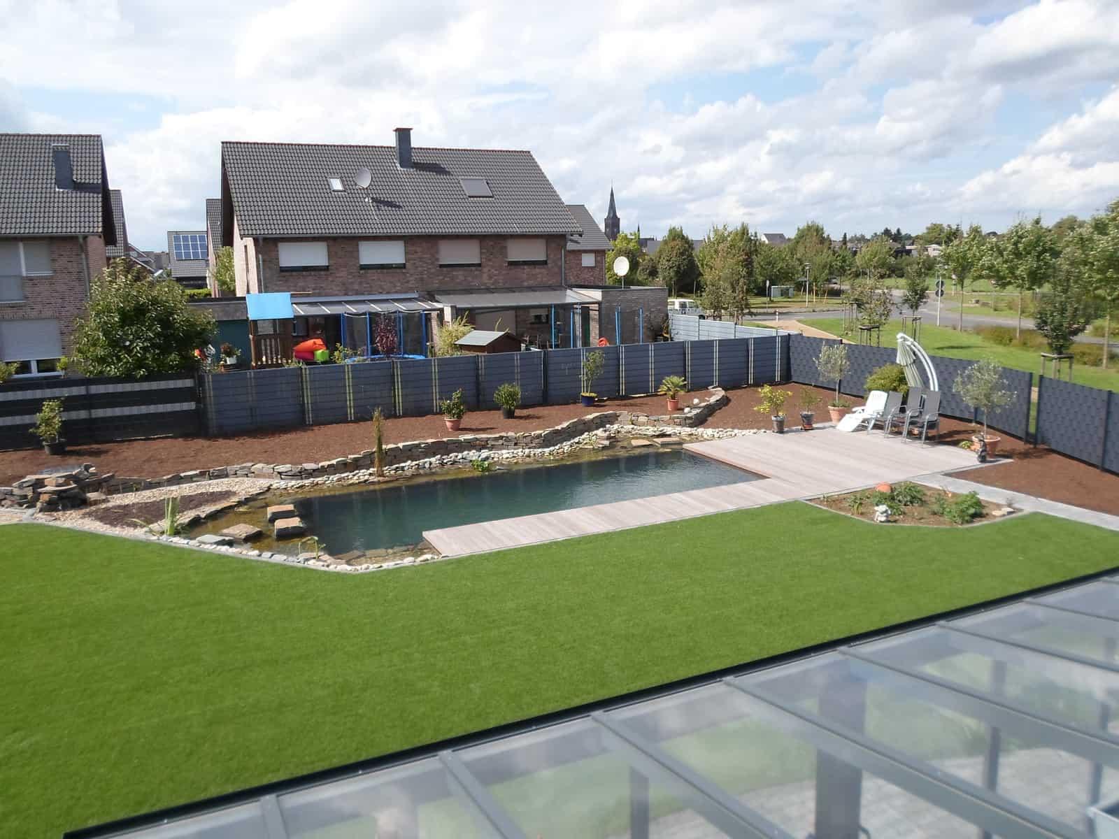 Schwimmteichanlage mit Holzterrasse und Natursteinmauer, Fertigrasen
